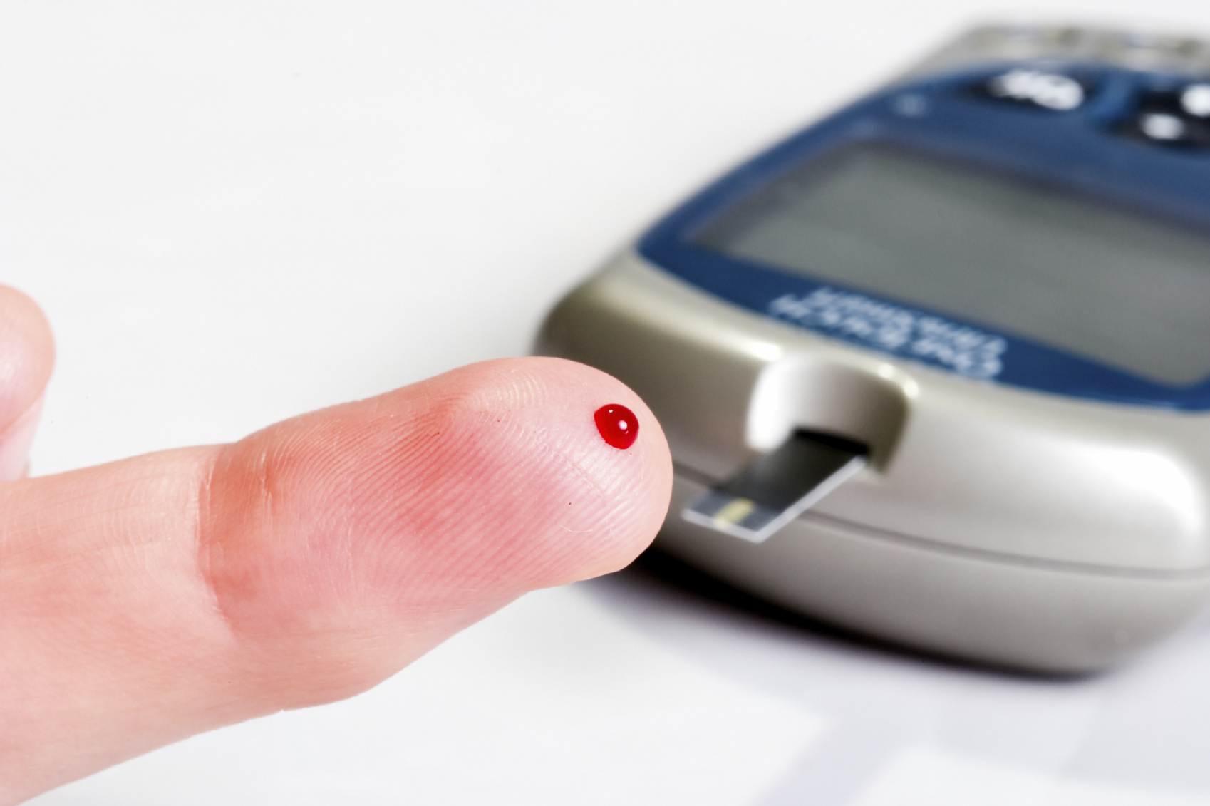 Diabetic is doing a glucose level finger blood test
